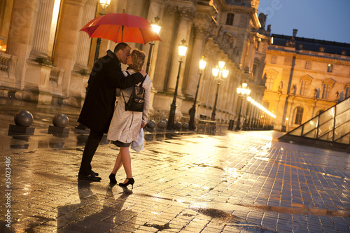 Caucasian couple kissing in rain at night at the Louvre