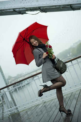 Caucasian woman in high heel shoes with red umbrella