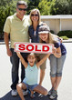 """Excited Caucasian family holding """"sold"""" sign"""