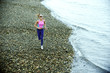 Caucasian woman running on pebble beach
