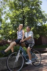 Caucasian man riding wife on handlebars
