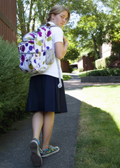 Caucasian school girl walking with backpack