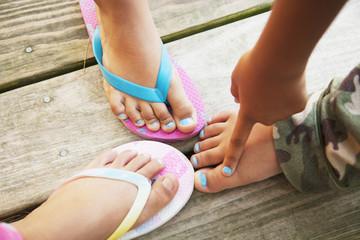 Hispanic children touching feet