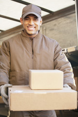 Smiling Hispanic delivery man carrying cardboard boxes