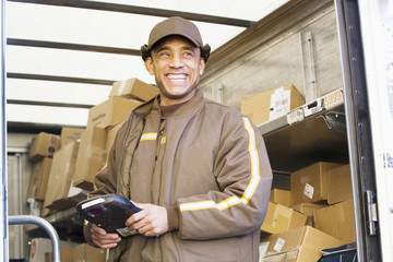 Smiling Hispanic delivery man standing in back of truck