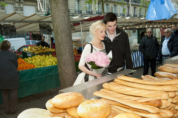 Caucasian couple shopping for bread at market