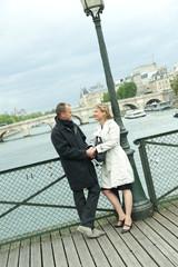 Caucasian couple holding hands on bridge