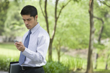 Hispanic businessman using cell phone in park