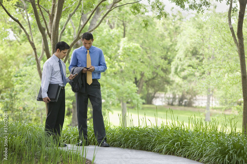 Hispanic businessmen using cell phones in park