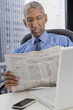 Mixed race businessman reading newspaper at desk