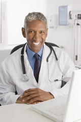 Mixed race doctor sitting at desk