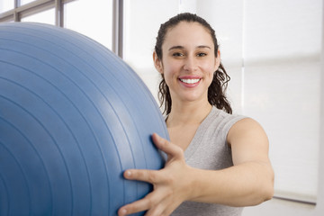 Mixed race woman holding large exercise ball