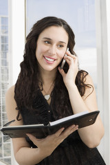 Mixed race businesswoman with notebook talking on cell phone