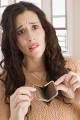 Mixed race woman opening empty coin purse