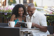 Couple in cafe looking at digital tablet together