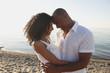 Couple hugging on beach near ocean