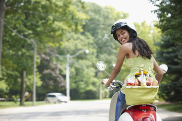Hispanic teenager riding scooter with groceries