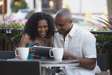 Couple with credit card in cafe looking at digital tablet together