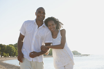 Couple walking on beach arm in arm