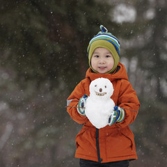 Chinese boy holding small snowman