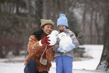 Chinese mother and daughter holding small snowmen