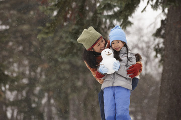 Chinese mother and daughter holding small snowman