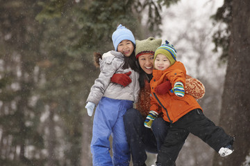 Chinese mother hugging children in snow