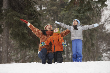 Chinese mother and children catching snowflakes on tongue