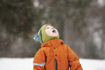 Chinese boy catching snowflakes on her tongue