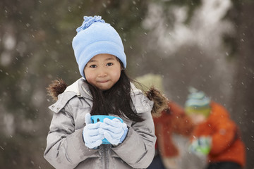 Chinese girl drinking hot chocolate in snow
