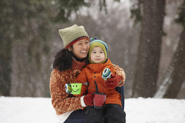 Chinese mother hugging son in the snow and drinking hot chocolate