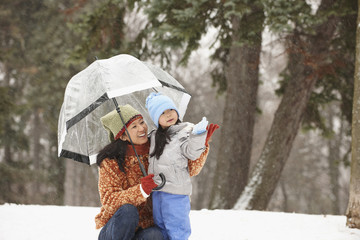 Chinese mother under umbrella with daughter