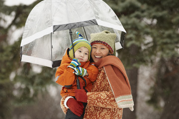 Chinese mother under umbrella with son