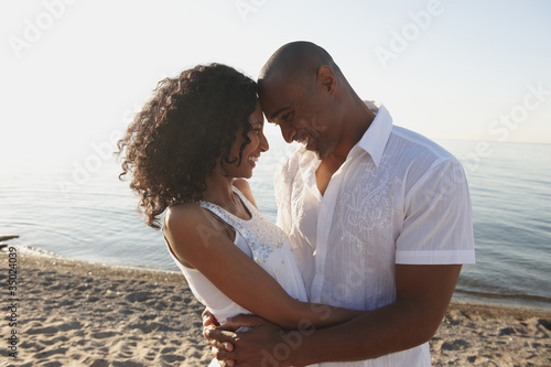 Couple hugging on beach near ocean