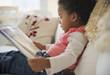 Black girl reading book on sofa