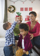 Black boy holding mistletoe over sister's head