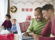 Black mother and father shopping online with credit card