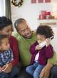 Black family watching girl talking on telephone