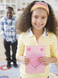 Smiling girl holding Valentine card