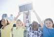 Children on rooftop holding up solar panel