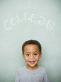 Black boy standing underneath the word college on blackboard