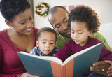Black family reading book together