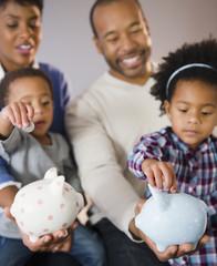 Black parents watching children put money in piggy bank