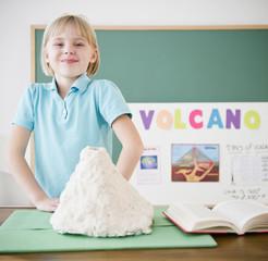 Caucasian girl standing with model volcano