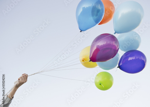 Caucasian woman holding bunch of balloons