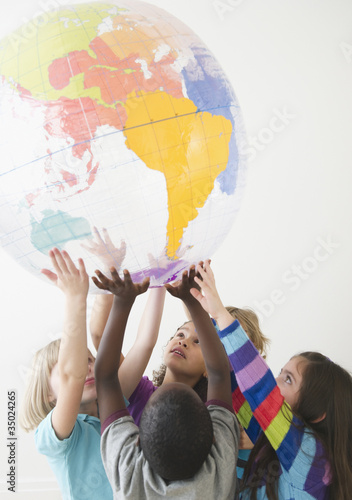 Children lifting up plastic globe