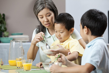 Asian mother feeding son cereal