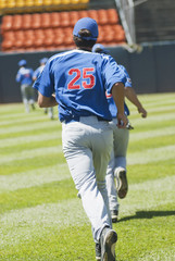 Hispanic baseball player running on field