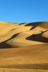 Blue sky and desert sand dunes