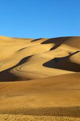 Blue sky and desert sand dunes